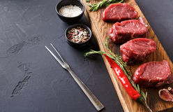 Filet mignon steaks and spices on wood at black background. Raw filet mignon steaks with herbs and spices. Cooking ingredients for restaurant dish. Fresh meat Stock Photography