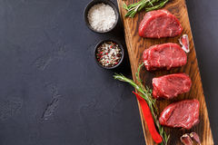 Filet mignon steaks and spices on wood at black background. Raw filet mignon steaks with herbs and spices. Cooking ingredients for restaurant dish. Fresh meat Royalty Free Stock Photos