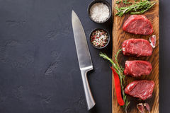 Filet mignon steaks and spices on wood at black background. Raw filet mignon steaks with herbs and spices. Ingredients for restaurant dish. Fresh meat, salt Royalty Free Stock Photo