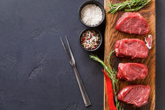 Filet mignon steaks and spices on wood at black background. Raw filet mignon steaks with herbs and spices. Ingredients for restaurant dish. Fresh meat, salt Stock Image