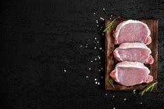 Filet rôti de biftecks de porc dans la poêle au-dessus du fond foncé, vue supérieure photos libres de droits
