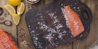 Filet saumoné cru avec les ris de veau et le sel de poivre sur le thème rustique de papier de cuisson avec le copie-espace Config Photo stock