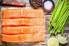 Filet saumoné cru frais avec la vue supérieure d'asperge et de chaux Photo libre de droits