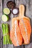 Filet saumoné cru frais sur une planche à découper en bois avec l'asperge Images libres de droits