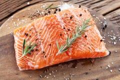 Filet saumoné sur un conseil de découpage en bois Images stock