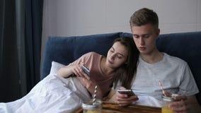 Filet surfant de couples mignons avec des smartphones dans le lit clips vidéos