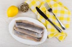 Filet van haringen, mes en vork op servet, citroen, specerij stock foto