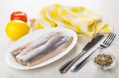 Filet van haringen in schotel, servet, citroen, tomaat, specerij, kni royalty-vrije stock afbeeldingen