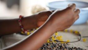 Filetage des perles en verre dans la fabrication simplement africaine, le Ghana banque de vidéos