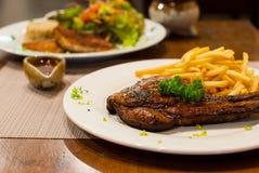 Filete asado a la parrilla chuleta de cerdo con las patatas fritas, top con perejil. Imagen de archivo libre de regalías