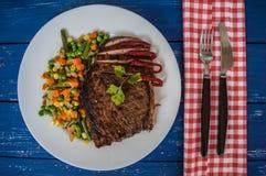 Filete asado a la parrilla con las verduras cocidas al vapor en una placa blanca Vector azul Visión superior Fotos de archivo