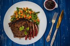 Filete asado a la parrilla con las verduras cocidas al vapor en una placa blanca Vector azul Visión superior Fotografía de archivo libre de regalías