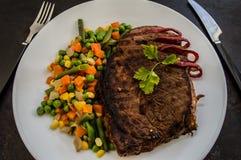 Filete asado a la parrilla con las verduras cocidas al vapor en una placa blanca Vector viejo Visión superior Foto de archivo libre de regalías