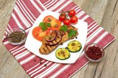 Filete asado a la parrilla con las verduras en la placa en una tabla de madera Imagenes de archivo