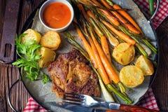 Filete asado a la parrilla con las verduras y las patatas fritas Imagen de archivo