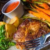 Filete asado a la parrilla con las verduras y las patatas fritas Fotos de archivo