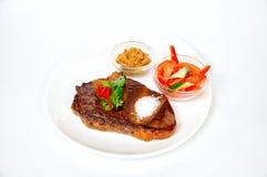 Filete asado a la parrilla del cerdo con los cuscurrones, la ensalada, la salsa y los tomates Foto de archivo libre de regalías