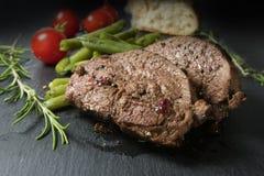 Filete asado a la parrilla del cordero con las habas verdes, los tomates y el romero en a Imágenes de archivo libres de regalías