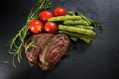 Filete asado a la parrilla del cordero con las habas verdes, los tomates y el romero en a Foto de archivo