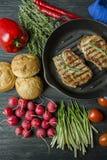 Filete asado a la parrilla en una cacerola redonda de la parrilla, adornada con las especias para la carne, el romero, los verdes foto de archivo libre de regalías