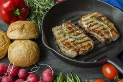 Filete asado a la parrilla en una cacerola redonda de la parrilla, adornada con las especias para la carne, el romero, los verdes imagen de archivo libre de regalías