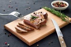 Filete bien hecho hecho en casa sabroso en tabla de cortar de madera con la bifurcación y cuchillo en el fondo de piedra Fotos de archivo
