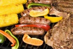 Filete, Bratwurst y maíz en la mazorca asados a la parilla Foto de archivo