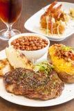 Filete con la patata, las habas y el pan de ajo cocidos Imagen de archivo libre de regalías