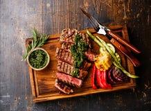Filete cortado de Striploin con la salsa y las verduras del chimichurri Foto de archivo libre de regalías