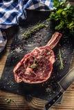 Filete crudo de la hacha de guerra de la carne de vaca con pimienta y romero de la sal en la placa de la pizarra fotos de archivo