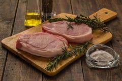 Filete crudo del cerdo con tomillo y romero en una tabla de cortar fotos de archivo libres de regalías
