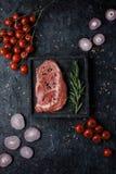 Filete crudo del ojo de la costilla de carne de vaca con los tomates, la cebolla y el romero en la opinión superior del fondo neg imagen de archivo