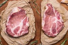 Filete crudo fresco del cerdo dos en el papel con cierre rústico de madera del fondo de las hierbas encima de la visión superior imagen de archivo libre de regalías