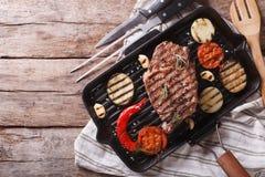 Filete de carne de vaca asado a la parrilla con las verduras en cacerola visión superior horizontal Imágenes de archivo libres de regalías