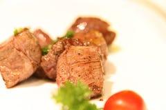 Filete de carne de vaca cúbico delicioso en un plato blanco Foto de archivo