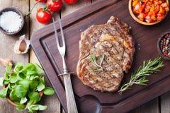 Filete de carne de vaca con el tomate y el romero de cereza en una opinión superior del fondo de madera oscuro de la tabla de cor Fotografía de archivo libre de regalías