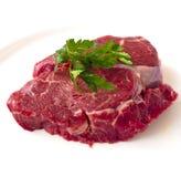 Filete de carne de vaca con la puntilla del perejil en el fondo blanco, aislada Fotos de archivo