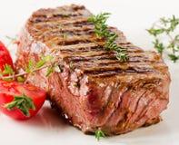 Filete de carne de vaca con las hierbas frescas en una placa blanca fotos de archivo