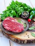 Filete de carne de vaca crudo con la sal y las pimientas en un backgraund de madera Fotos de archivo