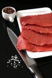 Filete de carne de vaca crudo, sal, pimienta y un cuchillo Fotografía de archivo libre de regalías