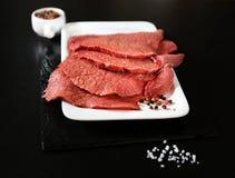 Filete de carne de vaca crudo, sal, pimienta y un cuchillo Foto de archivo