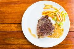 Filete de carne de vaca en el plato blanco con la ensalada y las patatas fritas Foto de archivo