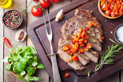 Filete de carne de vaca hecho bien con salsa del tomate y de la pimienta en un fondo de madera fotografía de archivo libre de regalías