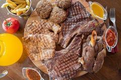 Filete de carne de vaca asado a la parrilla, cordero, chuletas con las patatas fritas y salsas encendido en tabla de cortar de ma Imagen de archivo
