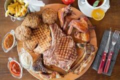 Filete de carne de vaca asado a la parrilla, costillas del cordero, alas de pollo con las patatas fritas y salsas encendido en ta Fotos de archivo libres de regalías