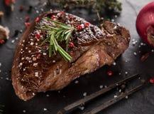 Filete de carne de vaca asado a la parrilla en la tabla de piedra negra fotos de archivo libres de regalías