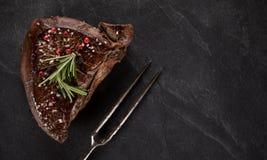 Filete de carne de vaca asado a la parrilla en la tabla de piedra negra Visi?n superior imagenes de archivo