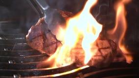 Filete de carne de vaca en la parrilla con las llamas metrajes