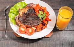 Filete de carne de vaca frito con las verduras y las habas en una placa fotos de archivo