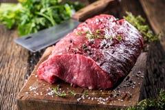 Filete de carne de vaca Filete de carne de vaca sin procesar Filete grande de Rib Eye en el tablero de madera con la sal y la pim imagen de archivo